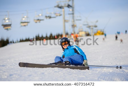 Young female skier in blue ski suit smiling after the fall on mountain slope against ski-lift. Ski resort at Carpathian Mountains. Winter sports concept. - stock photo