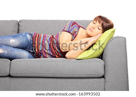 Young female sleeping on a sofa isolated on white background - stock photo