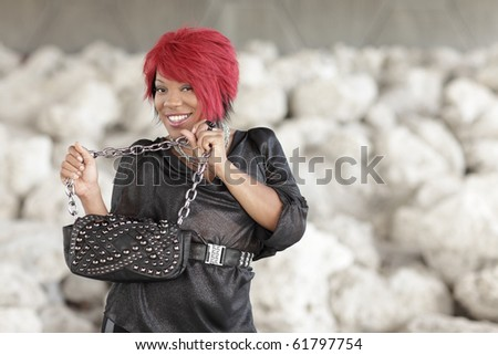Young female smiling and holding a handbag - stock photo