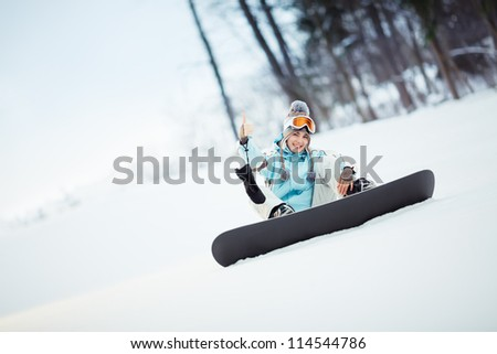 Young female snowboarder sitting on slope and showing thumb up, copy space