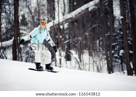 Young female snowboarder sliding down the slope, copy space