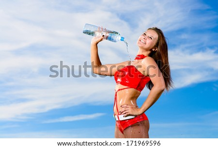 Young female sport girl in red uniform with a bottle of water - stock photo