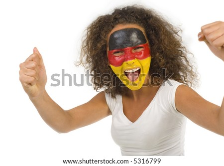 Young female sports fan with painted German flag on face. Front view. She's looking at camera. - stock photo