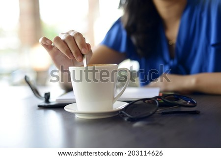 Young Female stir cup of coffee in the morning at Cafe - stock photo