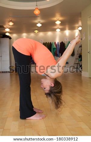 young female stretching in yoga studio - stock photo