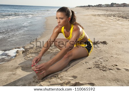 young female stretching outside on the beach - stock photo