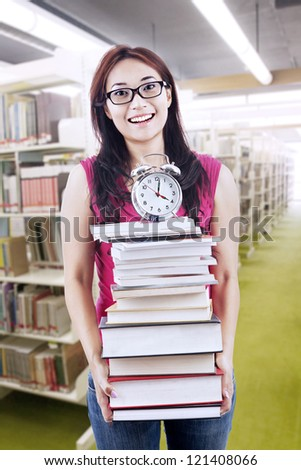 Young female student carrying stack of books with a clock on top - stock photo