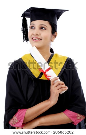 Young female student holding diploma and looking up against white