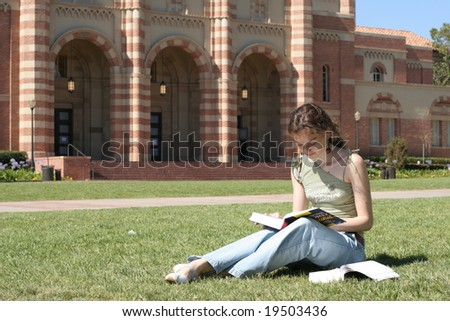 Young female student is reading in the campus - stock photo