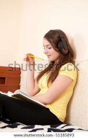 Young female student is thinking sitting in bed - stock photo