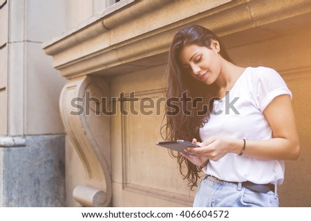 Young female student is using digital tablet while is standing near university building during work break. Stylish hipster woman is browsing internet for navigation in urban setting during recreation - stock photo