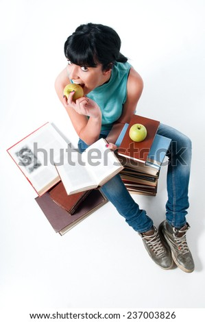 Young female student learning, sitting with books and eating apple - stock photo