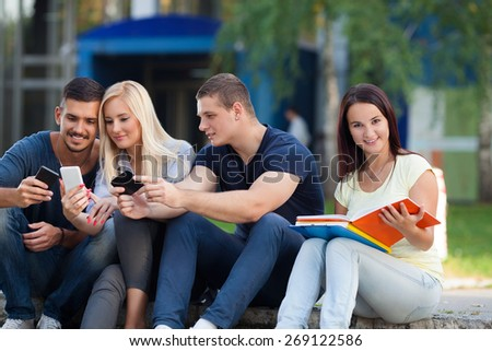 Young female student reading while her friends using thier mobile phones - stock photo