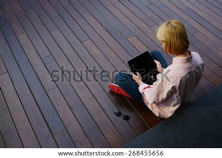 Young female student relaxing in a university recreation hall using touch pad, freelancer girl working on her digital tablet with big copy space,hipster woman using touchscreen device in modern office - stock photo
