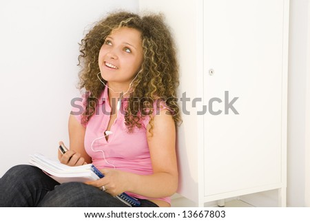Young female student sitting and leaning for shool locker. She's listening to music by headset. - stock photo
