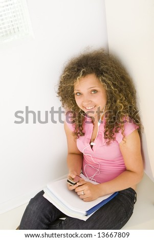Young female student sitting and leaning for shool locker. She's listening to music by headset. Looking at camera. High angle view. - stock photo