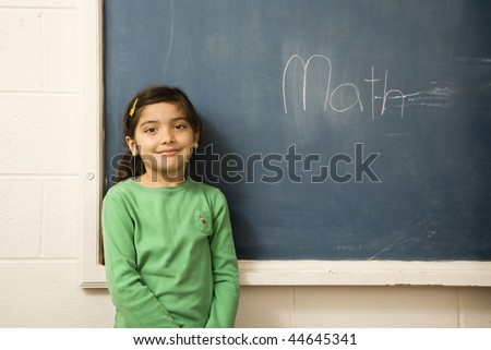 Young female student standing in front of blackboard with 'math' written on it. Horizontally framed shot. - stock photo
