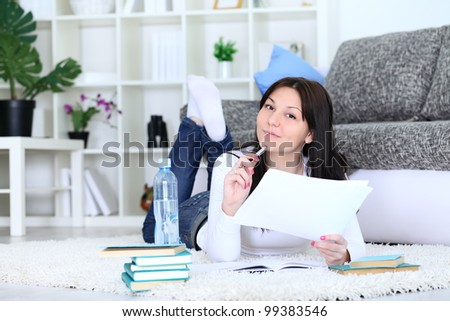 Young female  student thinking and smiling with book - stock photo