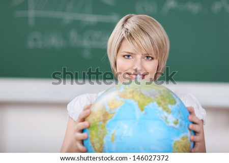 Young female student with a world globe held in her hands in front of her during a geography class at school or college - stock photo