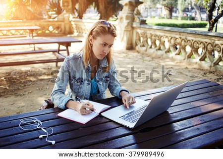 Young female student writes information from portable net-book while prepare for lectures in University campus,hipster girl working on laptop computer while sitting in city park during recreation time - stock photo