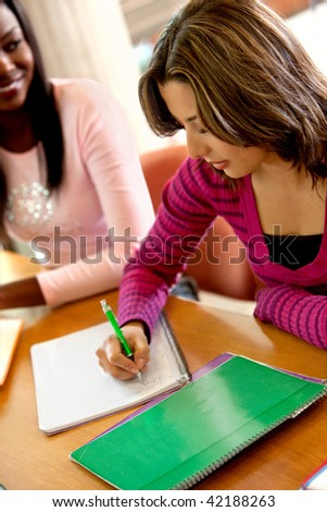Young female student writing on a notebook