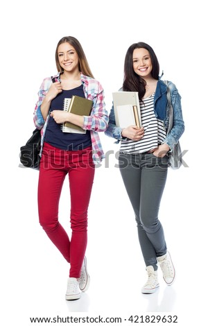 Young female students standing with books and bags, isolated on white - stock photo