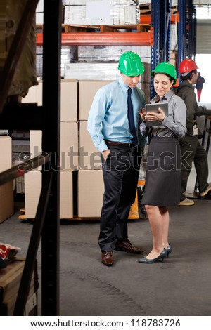 Young female supervisor and colleague using digital tablet at warehouse - stock photo