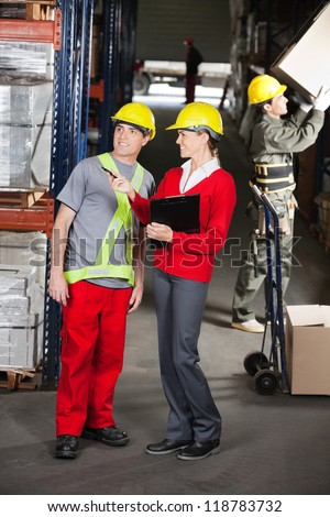Young female supervisor instructing foreman at warehouse