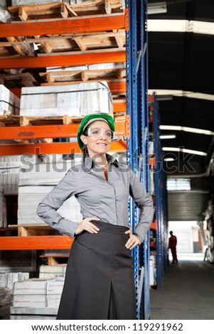 Young female supervisor wearing protective eyeglasses with hands on hips at warehouse