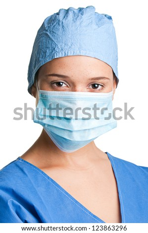 Young female surgeon with scrubs, holding a face mask on a white background