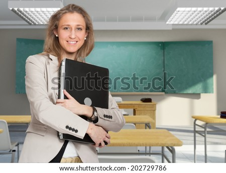 Young female teacher holding a laptop in a classroom - stock photo