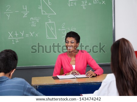 Young female teacher looking away while sitting at desk with students in foreground - stock photo
