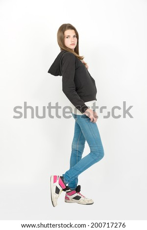young female teen girl blond hair wearing blue jeans and black jacket with hood - stock photo