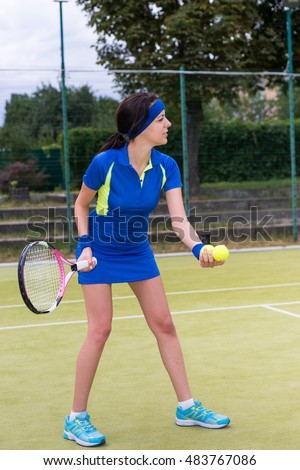 Young female tennis player preparing to serve wearing a sportswear during a match on a court outdoor in summer or spring