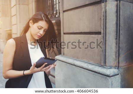 Young female tourist is viewing photos that she just took on touch pad camera during walking tour in the city, beautiful woman is searching information in network while is using her digital tablet  - stock photo