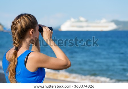 Young female tourist looking through binoculars at cruise ship (liner) and enjoying beautiful sea view. Woman wearing blue dress. Her hair braided in French plait. Outdoor portrait in summer. - stock photo
