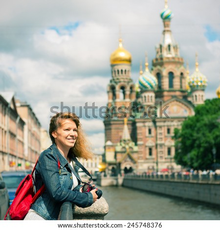Young female tourist near the Church of Savior on Spilled Blood (Cathedral of the Resurrection of Christ) in Saint Petersburg, Russia - stock photo