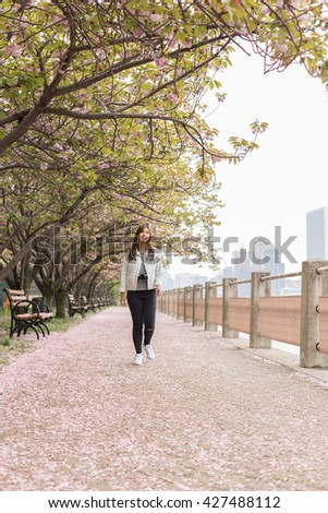 Young Female Tourist Walking under Cherry Blossom Trees in Roosevelt Islands, NYC