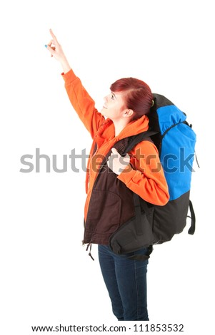 young female tourist with backpack pointing up, white background - stock photo