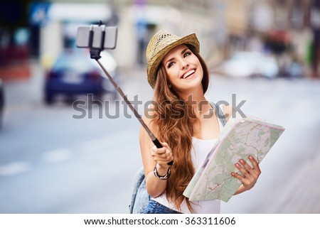 young female tourist with map taking selfie on city street - stock photo
