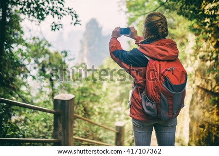 Young female tourist with red backpack among green foliage taking photo of beautiful mountain view in the Zhangjiajie National Forest Park, China. Her hair braided in French plait. Toned image. - stock photo