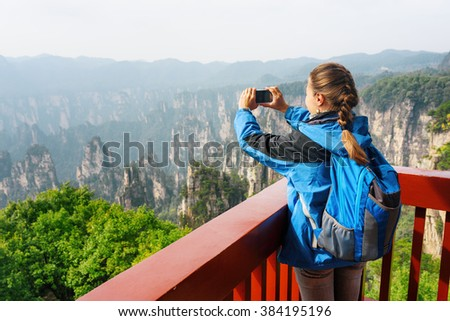 Young female tourist with smartphone taking photo and enjoying mountain view. The Zhangjiajie National Forest Park, Hunan Province, China. Her hair braided in French plait. Outdoor portrait. - stock photo