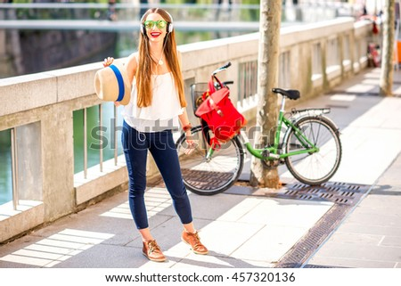 Young female traveler enjoying the music standing on the street with bicycle on the background in Ljubljana city. Traveling in Slovenia - stock photo