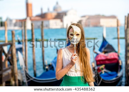 Young female traveler having fun with carnaval mask standing near San Marco square with gondolas on the background in Venice. - stock photo