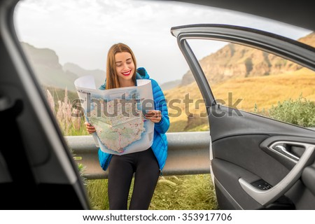 Young female traveler in blue jacket looking into the tourist map  near the car on the mountain road in Gran Canaria. View from inside the car with open doors - stock photo