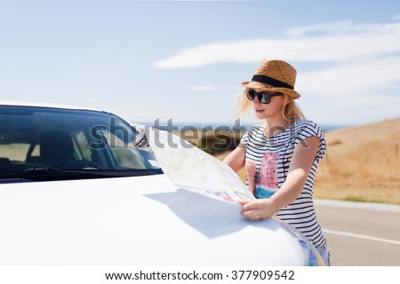 Young female traveler in hat looking into the tourist map standing near the car - stock photo