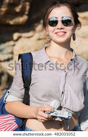 Young female traveller smiling with camera in hand