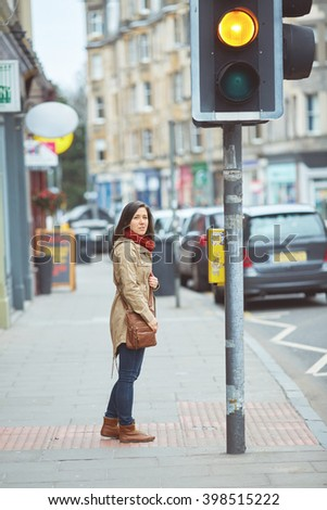 Young female trying to cross the street on the pedestrian crossing, traffic lights are changing - stock photo