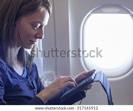 Young Female Using Digital Tablet During The Flight - stock photo