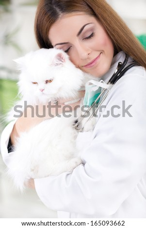 young female vet hugging white Persian cat